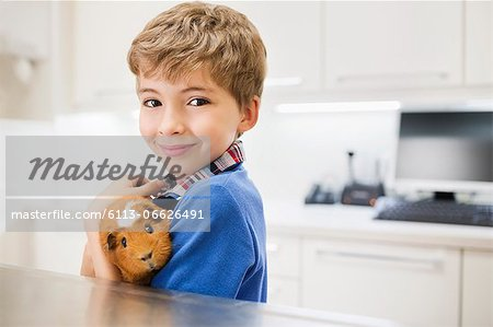 Boy holding guinea pig in vet's surgery Stock Photo - Premium Royalty-Free, Image code: 6113-06626491
