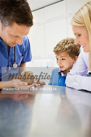 Veterinarian and owners examining guinea pig in vet's surgery Stock Photo - Premium Royalty-Free, Image code: 6113-06626514