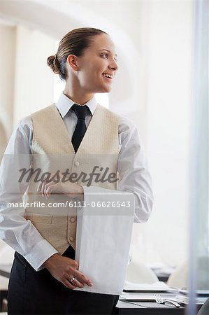 Waitress smiling in restaurant Stock Photo - Premium Royalty-Free, Image code: 6113-06626543