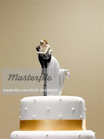 Bride and groom topper on wedding cake Stock Photo - Premium Royalty-Free, Image code: 6113-06626620