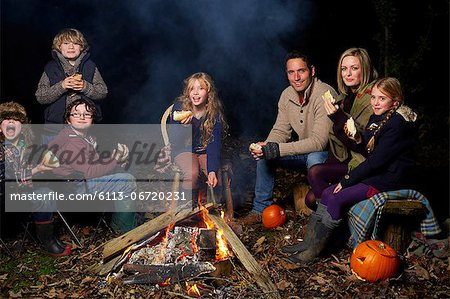 Family eating around campfire at night Stock Photo - Premium Royalty-Free, Image code: 6113-06720231