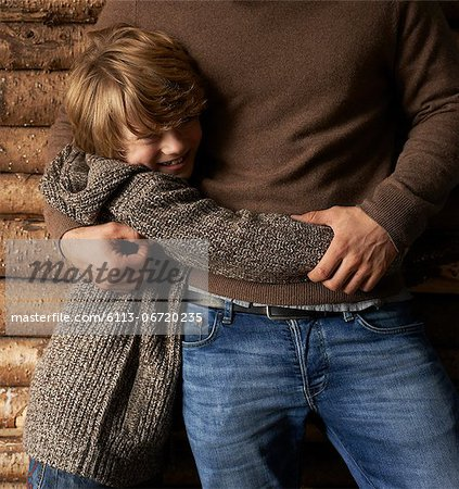 Smiling son hugging father Stock Photo - Premium Royalty-Free, Image code: 6113-06720235