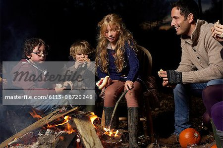 Family eating around campfire at night Stock Photo - Premium Royalty-Free, Image code: 6113-06720249