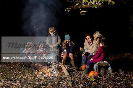 Family eating around campfire at night Stock Photo - Premium Royalty-Free, Image code: 6113-06720251