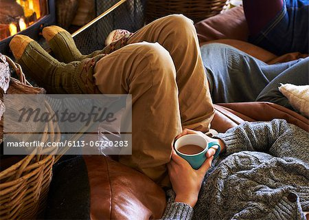 Boy drinking cup of coffee by fire Stock Photo - Premium Royalty-Free, Image code: 6113-06720283