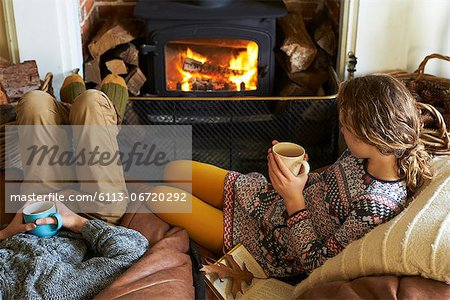 Children drinking cups of tea by fire Stock Photo - Premium Royalty-Free, Image code: 6113-06720292