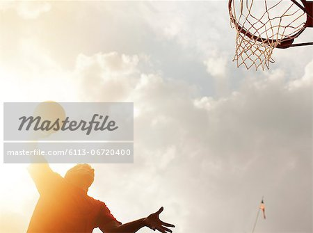 Man dunking basketball on court Stock Photo - Premium Royalty-Free, Image code: 6113-06720400