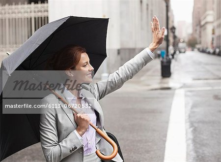 Businesswoman hailing taxi on city street Stock Photo - Premium Royalty-Free, Image code: 6113-06720532