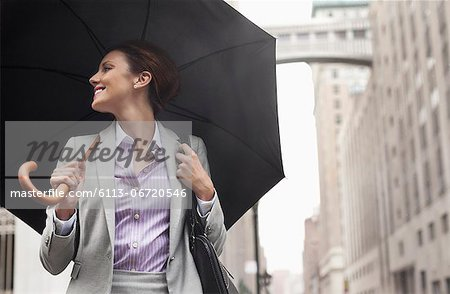 Businesswoman holding umbrella on city street Stock Photo - Premium Royalty-Free, Image code: 6113-06720546