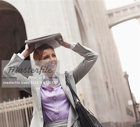 Businesswoman covering hair with newspaper Stock Photo - Premium Royalty-Free, Image code: 6113-06720557