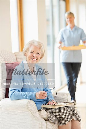 Older woman smiling in armchair Stock Photo - Premium Royalty-Free, Image code: 6113-06720639