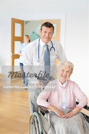 Doctor pushing older patient in wheelchair Stock Photo - Premium Royalty-Free, Image code: 6113-06720660