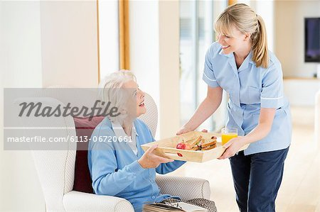 Caregiver giving older woman tray of food Stock Photo - Premium Royalty-Free, Image code: 6113-06720661