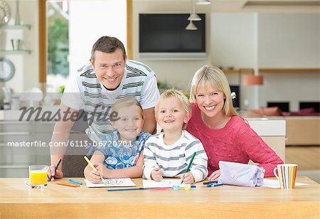Family smiling together at table Stock Photo - Premium Royalty-Free, Image code: 6113-06720701
