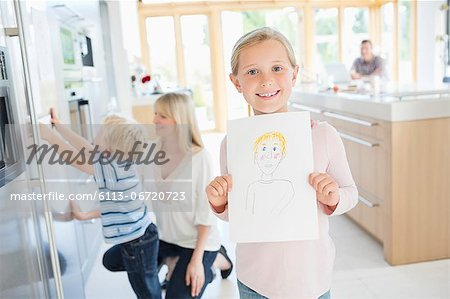Girl showing off drawing in kitchen Stock Photo - Premium Royalty-Free, Image code: 6113-06720723