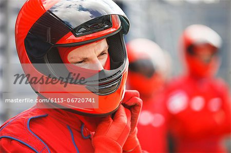 Racer tying on helmet on track Stock Photo - Premium Royalty-Free, Image code: 6113-06720741