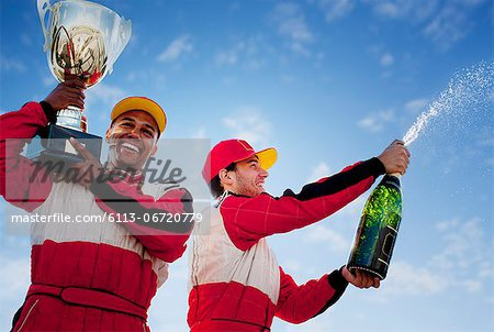 Racers holding trophy and champagne Stock Photo - Premium Royalty-Free, Image code: 6113-06720779