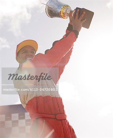 Racer holding trophy at award ceremony Stock Photo - Premium Royalty-Free, Image code: 6113-06720801