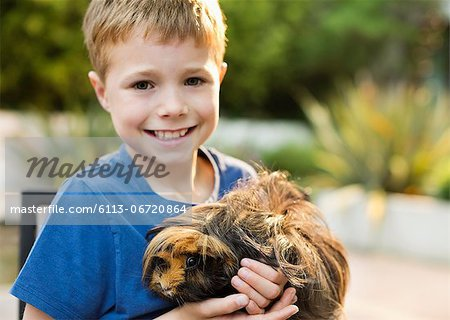 Smiling boy holding guinea pig outdoors Stock Photo - Premium Royalty-Free, Image code: 6113-06720864