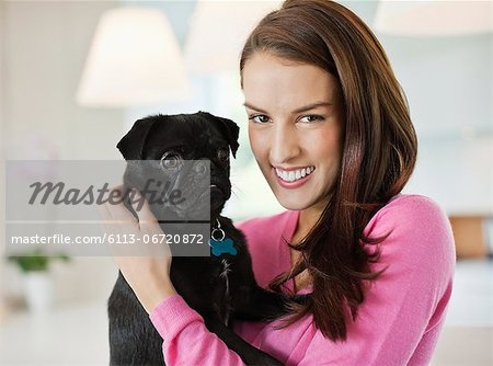 Smiling woman holding dog indoors Stock Photo - Premium Royalty-Free, Image code: 6113-06720872