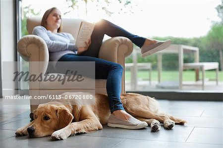 Dog sitting with woman in living room Stock Photo - Premium Royalty-Free, Image code: 6113-06720880