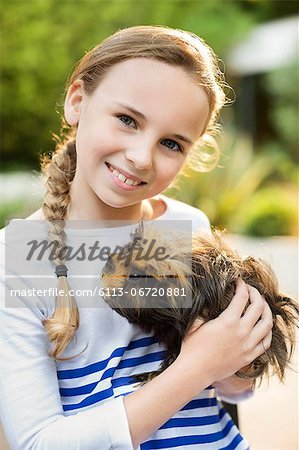 Smiling girl holding guinea pig outdoors Stock Photo - Premium Royalty-Free, Image code: 6113-06720881