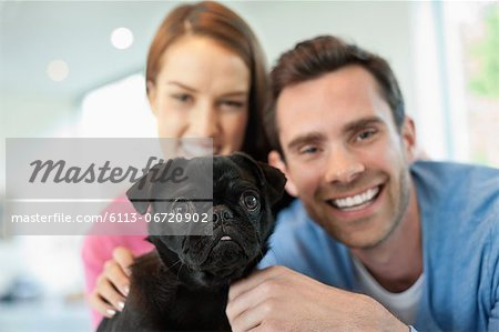 Smiling couple petting dog indoors Stock Photo - Premium Royalty-Free, Image code: 6113-06720902