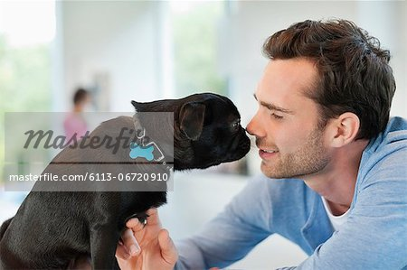 Man and dog touching noses indoors Stock Photo - Premium Royalty-Free, Image code: 6113-06720910