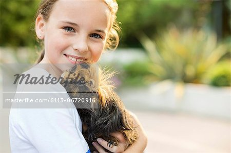 Smiling girl holding guinea pig outdoors Stock Photo - Premium Royalty-Free, Image code: 6113-06720916