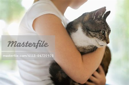 Girl holding cat indoors Stock Photo - Premium Royalty-Free, Image code: 6113-06720923