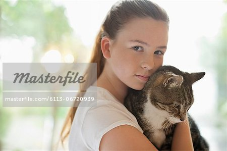 Girl holding cat indoors Stock Photo - Premium Royalty-Free, Image code: 6113-06720939