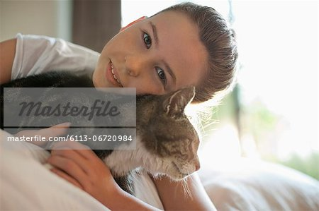 Girl petting cat on bed Stock Photo - Premium Royalty-Free, Image code: 6113-06720984