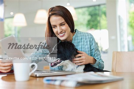 Woman with dog on lap using laptop Stock Photo - Premium Royalty-Free, Image code: 6113-06720989