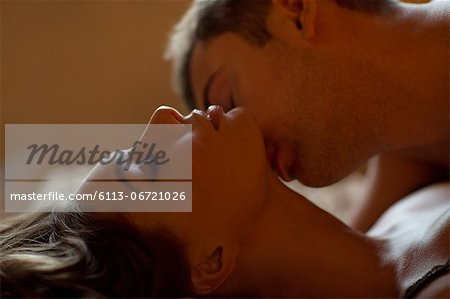 Couple kissing on bed Stock Photo - Premium Royalty-Free, Image code: 6113-06721026