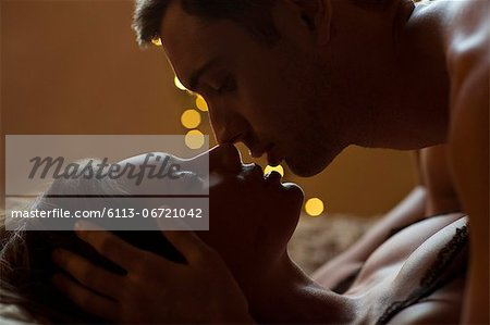 Couple kissing on bed Stock Photo - Premium Royalty-Free, Image code: 6113-06721042