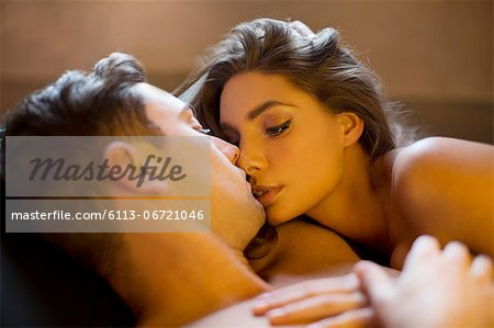 Nude couple kissing in bed Stock Photo - Premium Royalty-Free, Image code: 6113-06721046