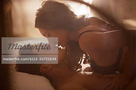 Couple kissing on bed Stock Photo - Premium Royalty-Free, Image code: 6113-06721049