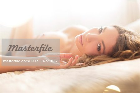 Nude woman laying on bed Stock Photo - Premium Royalty-Free, Image code: 6113-06721057
