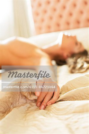 Nude woman gripping sheets on bed Stock Photo - Premium Royalty-Free, Image code: 6113-06721064