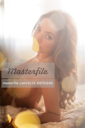 Nude woman laying on bed Stock Photo - Premium Royalty-Free, Image code: 6113-06721065