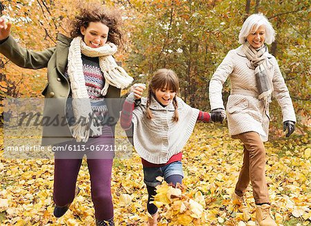 Three generations of women playing in autumn leaves Stock Photo - Premium Royalty-Free, Image code: 6113-06721140