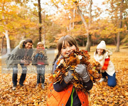 Family playing in autumn leaves Stock Photo - Premium Royalty-Free, Image code: 6113-06721183
