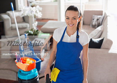 Maid smiling in living room Stock Photo - Premium Royalty-Free, Image code: 6113-06753203