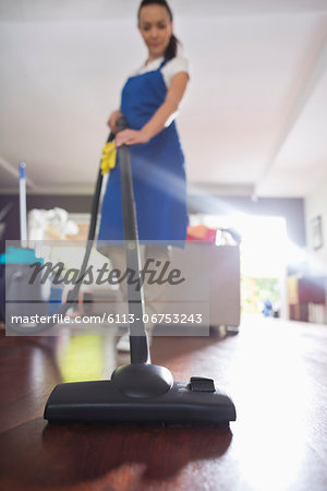 Woman vacuuming living room floor Stock Photo - Premium Royalty-Free, Image code: 6113-06753243