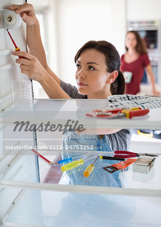 Female repair person working on fridge in home
