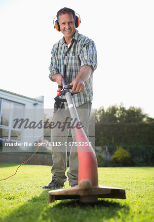 Man using weed whacker in backyard Stock Photo - Premium Royalty-Free, Image code: 6113-06753258