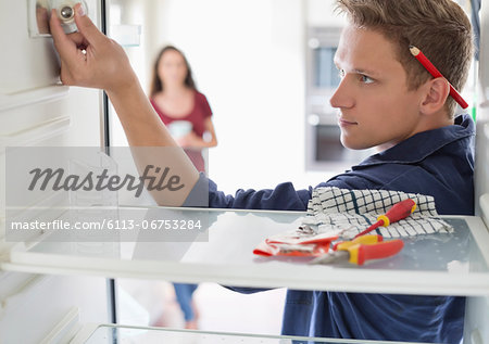 Electrician working on fridge in home Stock Photo - Premium Royalty-Free, Image code: 6113-06753284