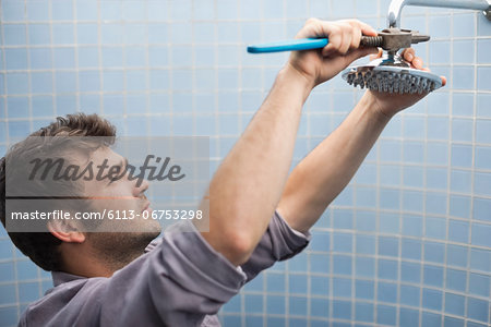 Plumber working on shower head in bathroom Stock Photo - Premium Royalty-Free, Image code: 6113-06753298