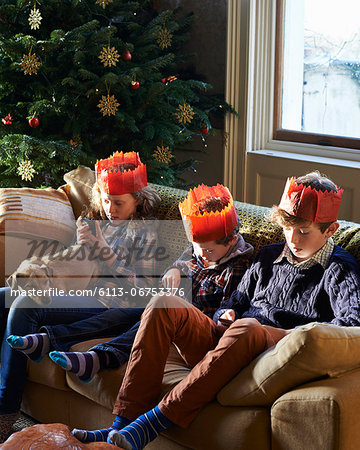 Children in paper crowns relaxing on sofa Stock Photo - Premium Royalty-Free, Image code: 6113-06753376