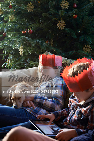 Children in paper crowns relaxing on sofa Stock Photo - Premium Royalty-Free, Image code: 6113-06753393